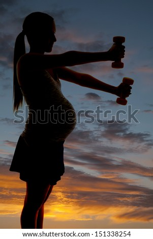 A pregnant woman silhouetted with weights. - stock photo