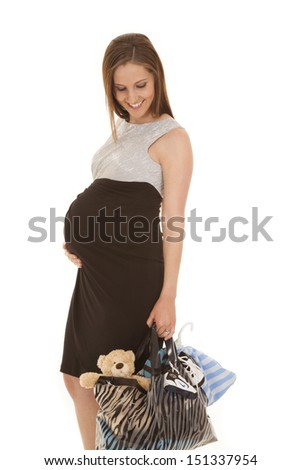 A pregnant woman standing with a shopping bag full.