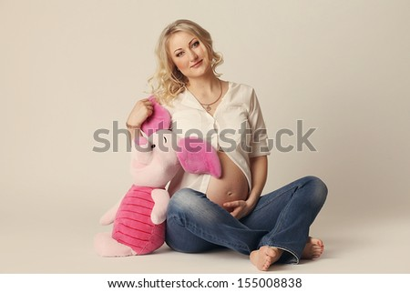 A pregnant woman with a plush toy in the hands of