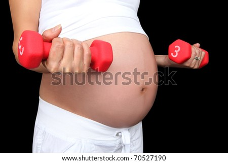 A pregnant woman working out with weights isolated over black - stock photo