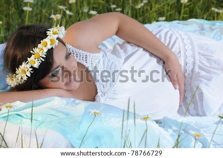 A pregnant young woman lay in bed in a field of flowers - stock photo