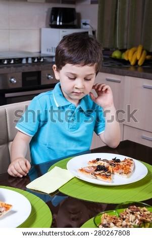 A preschool boy eat pizza in the kitchen - stock photo