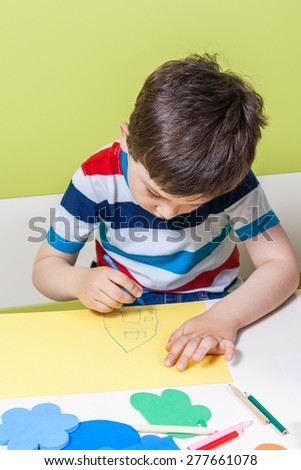 A preschool boy use a pencil for homework received from kindergarten