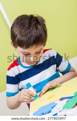 A preschool boy use glue for homework received from kindergarten