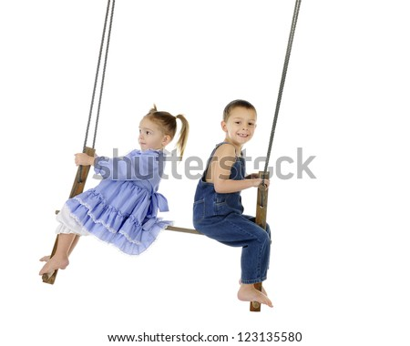 A preschool brother and sister swinging together on an antique 2-person pump swing.  On a white background with plenty of space for your text. - stock photo