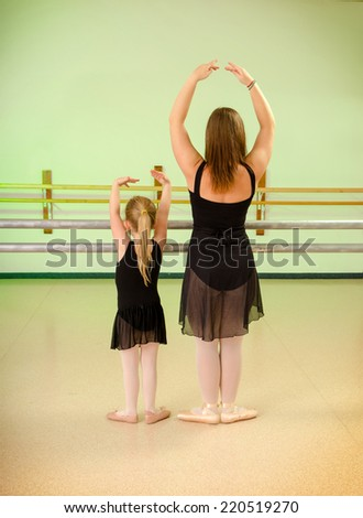 A Preschool Child with Teacher in Primary Ballet Class at Dance School Studio - stock photo