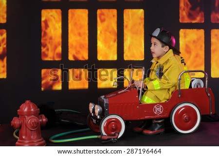 "A preschool ""fireman"" sitting in his vintage firetruck exclaiming about the blaze he sees through nighttime windows.   - stock photo"