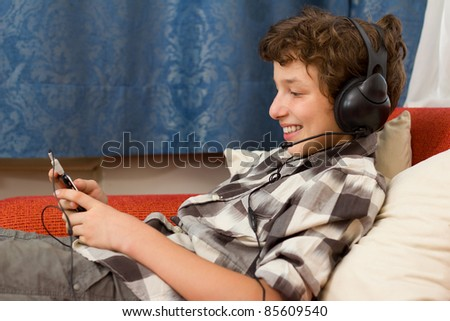 A preteen boy listening to music on his giant headphones as he sits back on an orange couch in a room with blue damask curtains. - stock photo