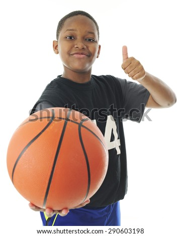 A preteen boy looking at and holding out his basketball for the viewer with a smile and a thumb's up.  Focus on boy.  On a white background.