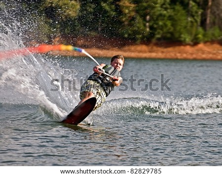 A preteen boy on a slalom ski cutting across the wake with an expression of total concentration. - stock photo