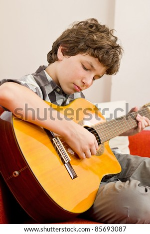 A preteen boy seated on an orange couch with white pillows plays a classic guitar with much feeling. - stock photo