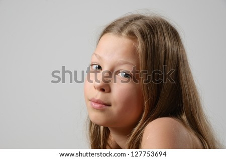 A preteen girl is photographed on the gray background. The serene child is looking at the camera. Her fair long hair are flowing. - stock photo