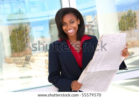 A pretty african american business woman at office reading newspaper - stock photo