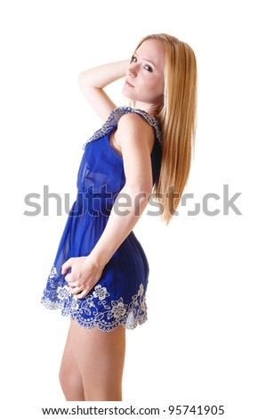 A pretty and slim young woman standing in her blue short dress and  long blond hair for white background in the studio. - stock photo