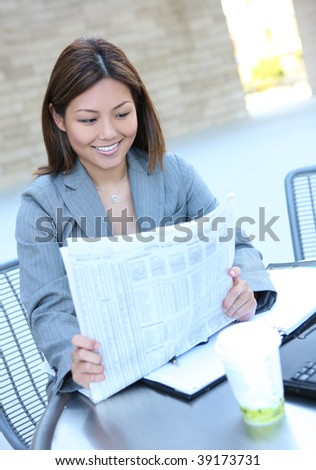 A pretty asian business woman at office reading newspaper - stock photo