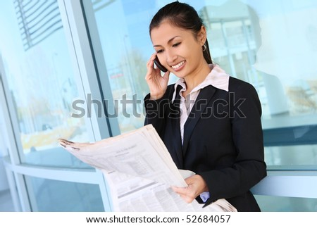 A pretty asian business woman on the phone at office building - stock photo