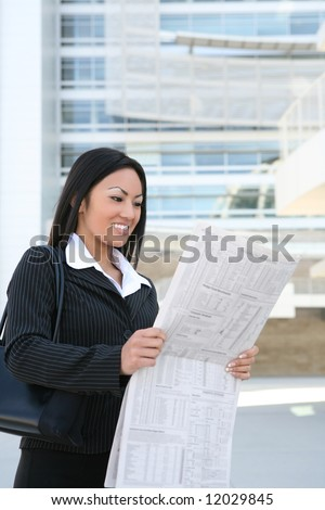 A pretty asian business woman reading the newspaper outside company - stock photo