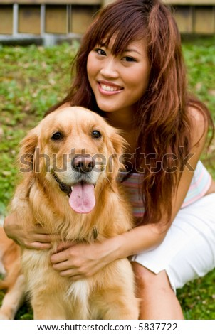 A pretty asian women outside with a dog