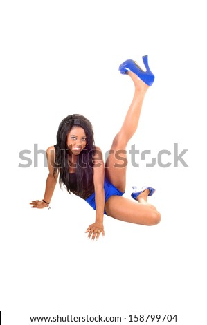 A pretty black slim woman sitting on the floor holding one leg up, for white background, in blue shorts and high heels.