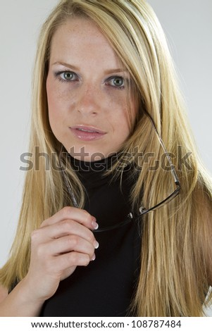 A pretty blond girl looking intently into the camera after just taking off her eyeglasses. - stock photo