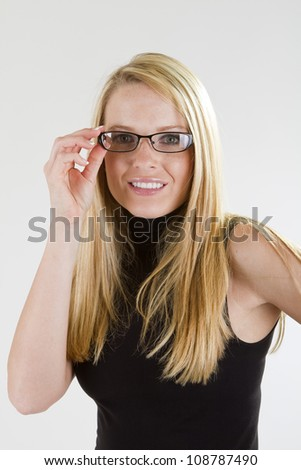 A pretty blond girl wearing glasses and smiling.