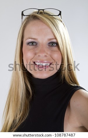 A pretty blond girl with her eyeglasses on top of her head smiles big for the camera.