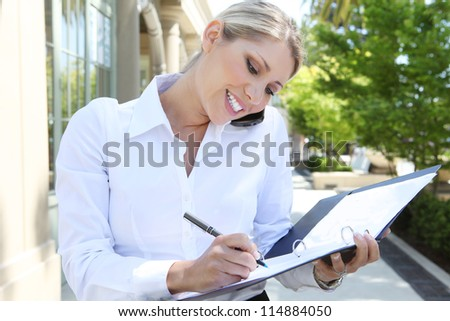 A pretty blonde business woman at office on the phone - stock photo