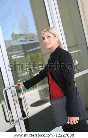 A pretty blonde business woman entering her company - stock photo