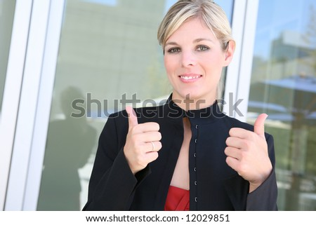 A pretty blonde business woman with her thumbs up - stock photo