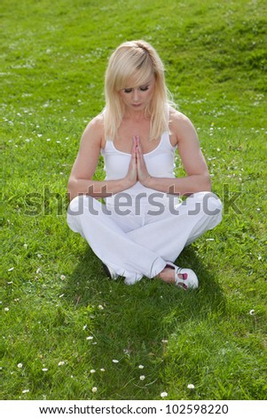 A pretty blonde girl sits on the green grass with her head bowed and hands clasped together in prayer seeking serenity through yoga - stock photo