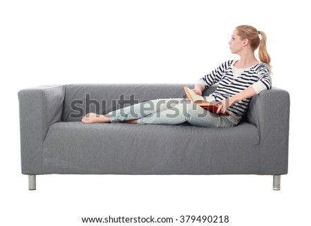 a pretty blonde lady wearing casual clothes, lounging on a grey sofa. isolated on a white background.