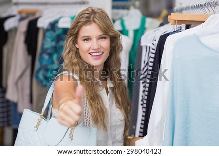 A pretty blonde woman smiling and thumbs up in the clothing store