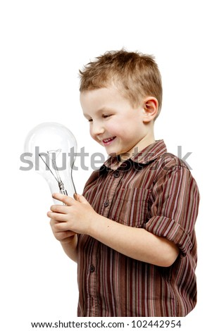 A pretty boy is holding in the hands of the bulb. He is satisfied, smiling and happy. - stock photo