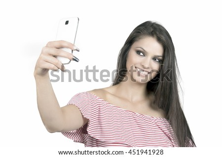 A Pretty brunette girl doing a selfie with her smart phone  - stock photo