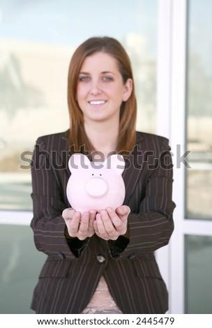 A pretty business holding a piggy bank (focus on piggy bank) - stock photo