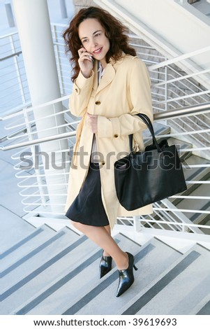 A pretty business on the stairs on phone at company - stock photo