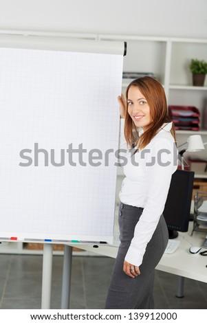 A pretty business woman making a presentation on a flipchart - stock photo