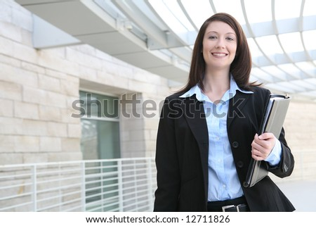 A pretty business woman talking on the phone at office building - stock photo