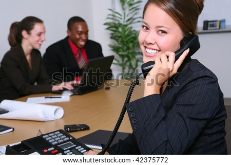 A pretty business woman with her team in the office - stock photo