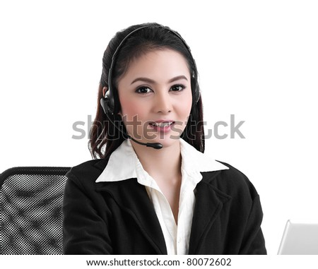 A pretty call center woman in headset talking with customer - stock photo