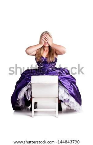 a pretty caucasian girl wearing a purple ball gown sitting on a white chair and holding her hands over her eyes
