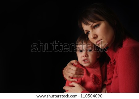 A pretty Caucasian mama with a sad crying daughter on a dark background - stock photo
