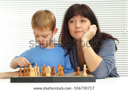 A pretty Caucasian mother and son playing chess against a light background