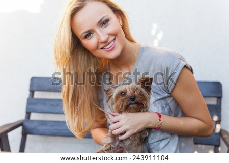 A pretty caucasian woman at home sitting on the porch and playing with a dog. Outdoor photo. - stock photo