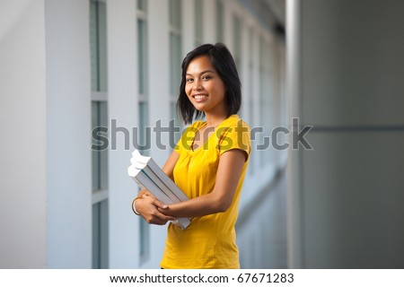 A pretty college student stands smiling with books in a modern hallway on a university campus.  Young female Asian Thai model late teens, early 20s of Chinese descent. - stock photo