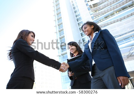 A pretty diverse young business woman team at office building handshake