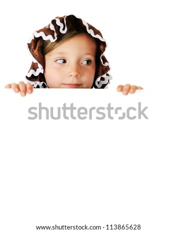 A pretty elementary gingerbread girl looking to the right as she peeks over a white sign (left blank for your text).  On a white background. - stock photo