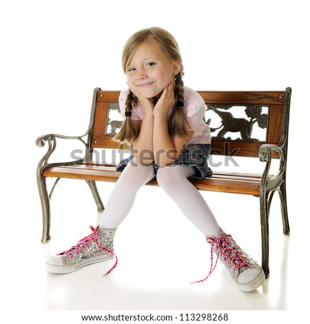 A pretty elementary girl sitting on a bench, delighted with her over-sized, high-top, sparkly sneakers.  On a white background. - stock photo