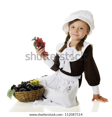 A pretty elementary Pilgrim girl happily sitting with a basket of fruit.  On a white background. - stock photo