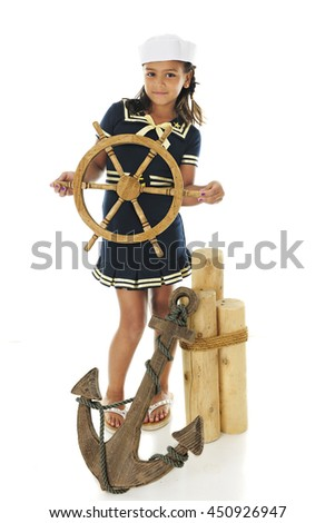 "A pretty elementary ""sailor  girl"" looking at the viewer as she stands by mooring posts, an anchor and holding a ship's wheel.  On a white background."